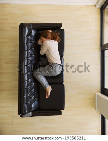 Overhead view of young woman sleeping on sofa by a door. Aerial view of caucasian female relaxing on couch at home. - stock photo