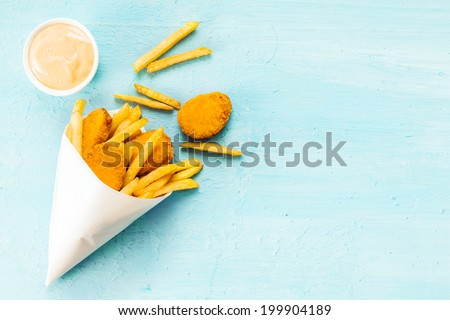 Overhead view on a blue background with copyspace of medallions of fried fish and chips in a takeaway paper cone with savory mayonnaise dip - stock photo