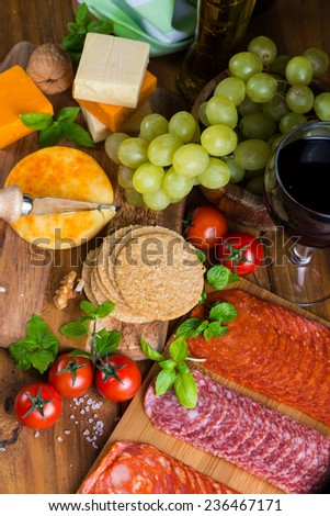 overhead view on antipasti with cheese salami ham red wine and grapes - stock photo
