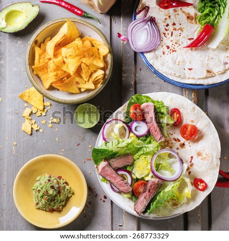 Overhead view on mexican style dinner with tacos, vegetables, nachos chips and guakomole, served over gray wooden table. - stock photo