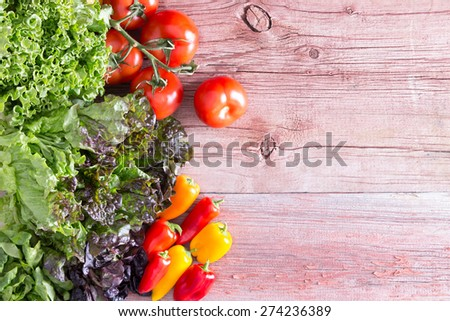 Overhead view on rustic wooden boards with peeling paint of three different lettuce varieties with fresh tomatoes and red and orange mini bell peppers, with copy space - stock photo