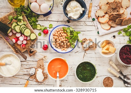 Overhead view on vegetarian style dinner with pumpkin, beetroot, spinach soup cream and chickpeas dish with fresh vegetables and cream cheese, yogurt sauce, sesame seed, butty bread on a white table - stock photo