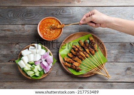 Overhead view people holding chicken satay dipping peanut sauce on wooden dining table, one of famous local dishes. - stock photo