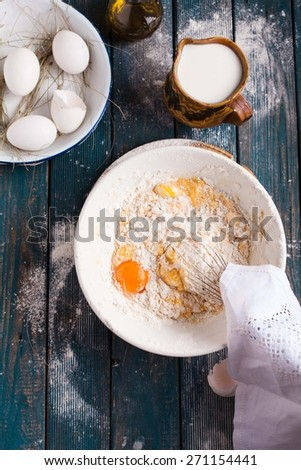 Overhead with working dough on bowl on wooden kitchen table with raw ingredients and utensil. Rustic food background. See series. - stock photo
