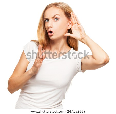 Overhears a woman put her hand to her ear - stock photo