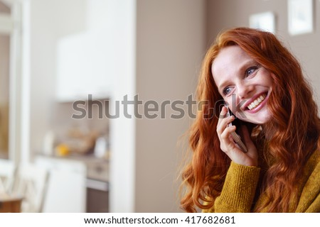 Overjoyed beautiful single Caucasian woman with long red hair on mobile phone and copy space to the side - stock photo