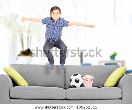 Overjoyed boy jumping on couch at home shot with tilt and shift lens - stock photo