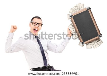 Overjoyed businessman holding a briefcase full of money isolated on white background - stock photo