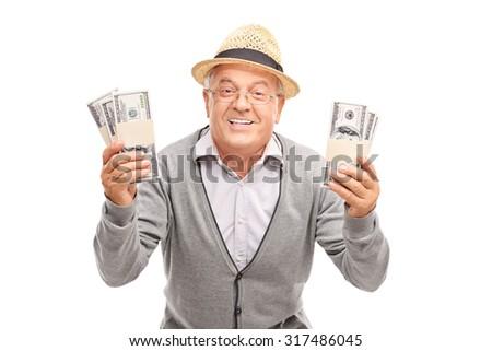 Overjoyed senior gentleman holding two stacks of money and smiling isolated on white background - stock photo