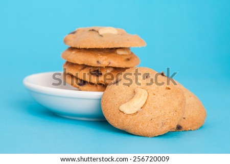 overlap of cookies cashew nut and chocolate chip put on the white plate on blue background - stock photo