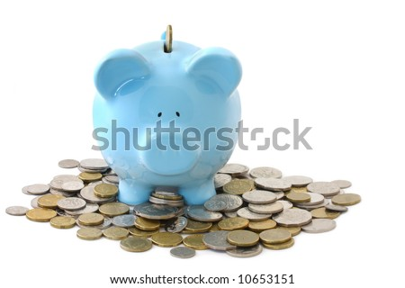 Overloaded blue piggy bank, surrounded by gold and silver coins. - stock photo