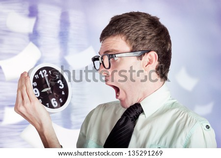 Overloaded businessman standing in a modern office flooded with paper work holding over time clock with look of stress - stock photo