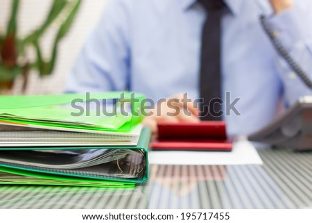 overloaded consultant in blur with stack of binders and speaking on phone - stock photo