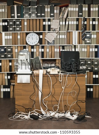 Overloaded desk at a messy office - stock photo