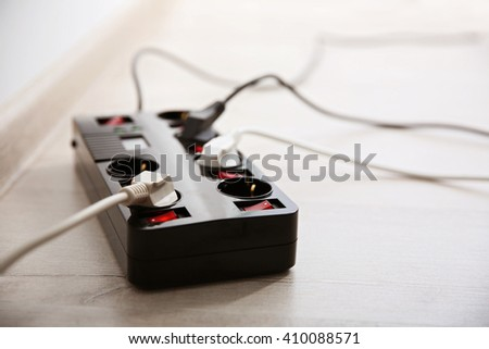 Overloaded power board on parquet, indoors - stock photo