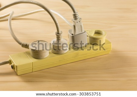 Overloaded power boards on wooden floor - stock photo