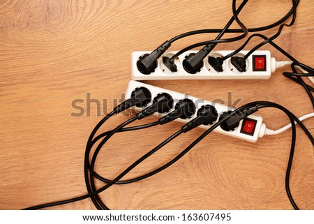 Overloaded power boards, on wooden floor background - stock photo