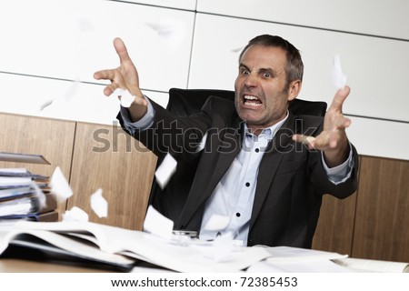 Overloaded senior businessman being upset about work, tearing papers and screaming, sitting at office desk in front of many books and files.
