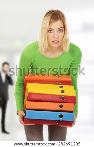 Overloaded woman with heavy binders. - stock photo