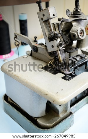 overlock sewing machine on the work table close up. vertical - stock photo