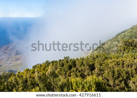 Overlook from the Mirador de Alojera to the canyon Barranco del Mono with the village Alojera. Trade winds with huge clouds comes from the north into the valley. The clouds comes from the Azores - stock photo