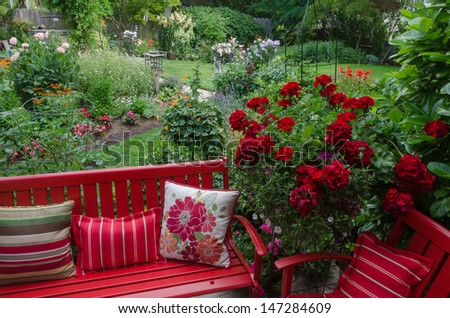 Overlooking a colorful backyard garden with casual red furniture and geraniums.in the foreground. - stock photo