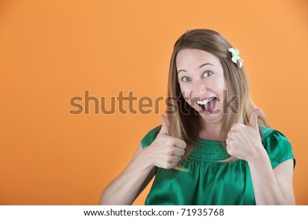 Overly enthusiastic woman in green blouse with thumbs up - stock photo
