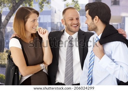 Overly happy, annoying businessmen celebrating with startled female colleague after work, outdoors. - stock photo
