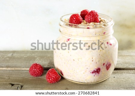 Overnight breakfast oats with raspberries in a mason jar on wood - stock photo