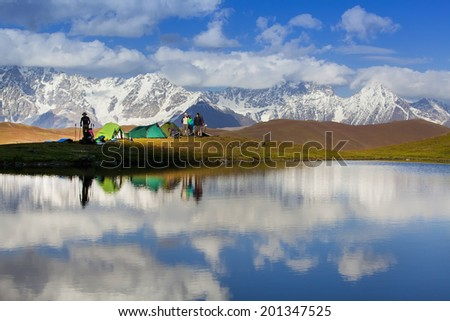 Overnight group of tourists in the camp on the shore of a quiet lake, on the back of high snowy mountains in the starry night.  - stock photo