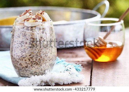 Overnight oats made with Chia seeds and fresh sliced bananas. Garnished with shaved chocolate and drizzeled honey and served outdoors. Extreme shallow depth of field. - stock photo