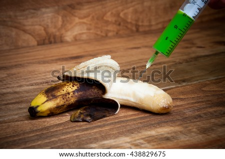 Overripe banana being injected with a syringe - stock photo