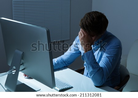 Overstressed businessman leaning at computer desk in office - stock photo