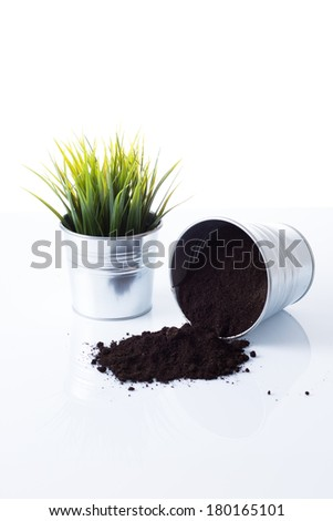 Overturn plant pots with soil and grass - stock photo