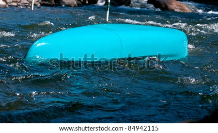 Overturned canoe in fast water - stock photo