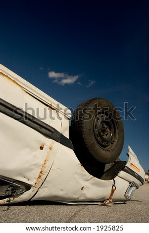 Overturned car on the road, front wheel shown, against deep blue sky