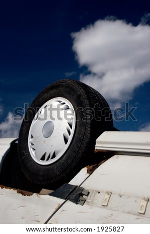 Overturned car, wheel in the air, against deep sky - stock photo