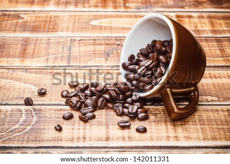 Overturned coffee cup with beans - stock photo