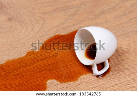 Overturned cup of coffee on floor close-up - stock photo