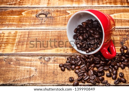 Overturned cup with coffee beans - stock photo
