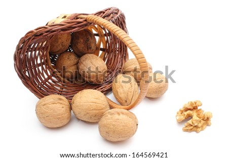 Overturned wicker basket with brown walnuts. Isolated on white background - stock photo
