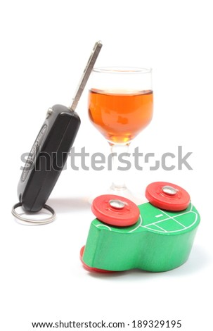 Overturned wooden toy car with glass of wine and car key, car key and alcohol, don't drink and drive concept. Isolated on white background - stock photo