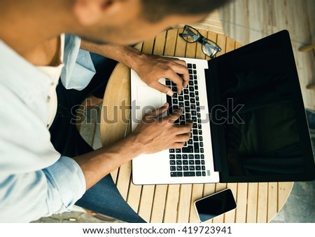 Overview of a man working on laptop - stock photo