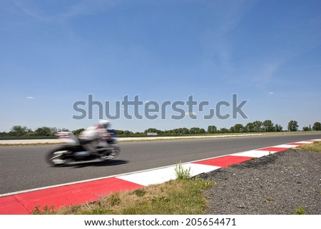Overview of a motorsports circuit with a race bike driving past - stock photo