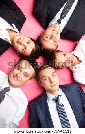 Overview of business people lying together and looking at camera with a smile