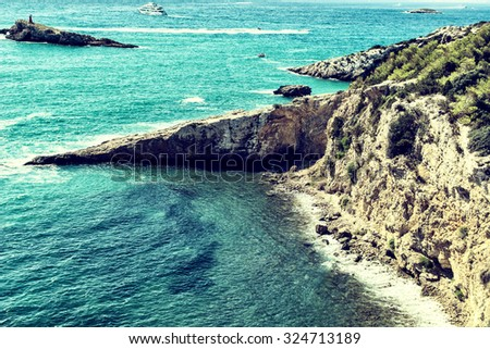 Overview of Isolated Deserted Sand Beach Along Rocky Cliff Lined Coast with Turquoise Waters on Coast of Ibiza, Spain on Sunny Day with Yachts in Distance - stock photo