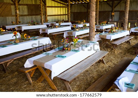 Overview of this wedding reception shows the tables ready for guests with organic natural decor and decorations. - stock photo