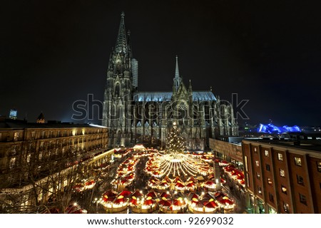 Overview over the Christmasmarket with the Cologne Cathedral. Part of the UNESCO Worldheritage. The most visited object of interest in Germany is 157.38 m tall. - stock photo