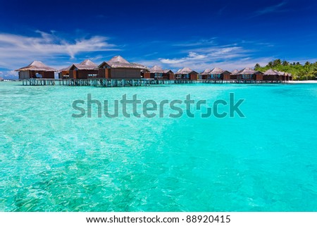 Overwater bungallows in blue lagoon around tropical island - stock photo