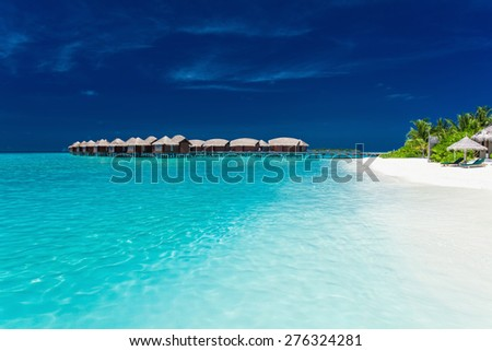 Overwater bungallows in blue lagoon on tropical island with palm trees - stock photo
